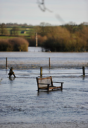 © Licensed to London News Pictures. Date 24 December 2013. Ascott Under Wychwood. Deserted bench by the river Evenlode. Flooding images - River Evenlode in full flood.. Photo credit : MarkHemsworth/LNP