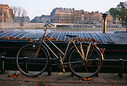 A trusting owner has left their bicycle leaning, unlocked, against a railing near a barge on left-bank of  Seine, Paris.