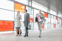 Businesspeople walking while male colleague rushing in railroad station