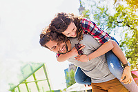 Portrait of young attractive man giving his girlfriend piggy ride back