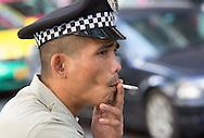 Security Guard smoking a cigarette, Bangkok.
