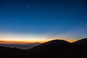Sky fades from orange to dark blue at twilight in the distance behind Hualalai volcano seen from Mauna Kea's Sunset Hill. Hualalai (8271 feet elevation, the small bump in the far distance) is the westernmost and third-youngest of the five shield volcanoes that form the island of Hawaii. Hualalai rose above sea level about 300,000 years ago. Last erupted in 1801, Hualalai is still active and may erupt again within the next century, which will be a rude shock to the town of Kailua-Kona built on its flanks. For colorful sunset views of the Saddle Road region, walk 1 mile round trip (160 ft gain) to the cinder cone of Pu'u Kalepeamoa, or Sunset Hill, from the Onizuka Center for International Astronomy Mauna Kea Visitor Information Station at 9200 ft elevation. About a million years old and last erupted 6000 to 4000 years ago, Mauna Kea is a dormant volcano on the Big Island of Hawaii, USA. Mauna Kea stands 13,800 feet above sea level and is the highest point in the state of Hawaii. Measured from its base on the ocean floor, it rises over 33,000 ft, significantly greater than the elevation of Mount Everest above sea level. Paving ends at the Visitor Info Station, and four-wheel drive is recommended to reach the top, where Mauna Kea summit's dry, clear, stable air makes one of the world's best sites for astronomy.