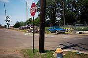 Neglected cars sit by the train tracks leading into the Baptist Town neighborhood in Greenwood Mississippi on Wednesday, May 19, 2010.