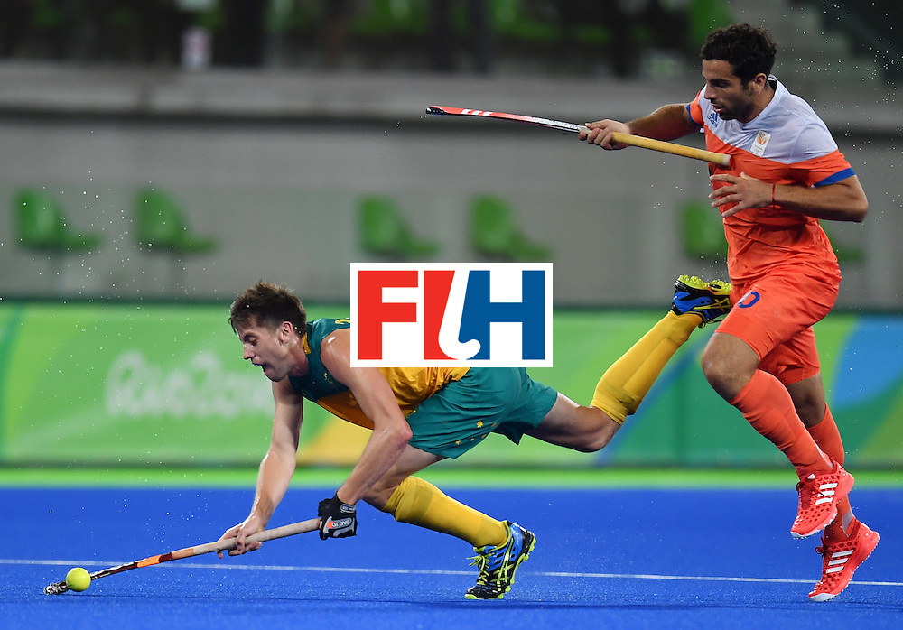 TOPSHOT - Australia's Eddie Ockenden (L) falls on the pitch as he vies with Netherland's Valentin Verga during the men's quarterfinal field hockey Netherlands vs Australia match of the Rio 2016 Olympics Games at the Olympic Hockey Centre in Rio de Janeiro on August 14, 2016. / AFP / MANAN VATSYAYANA        (Photo credit should read MANAN VATSYAYANA/AFP/Getty Images)
