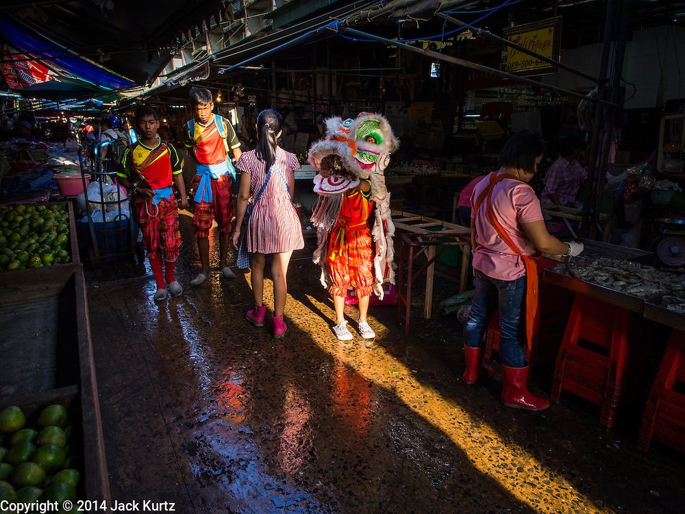 19 NOVEMBER 2014 - BANGKOK, THAILAND: Chinese lion dancers walk down a lane between market stalls in Khlong Toei Market in Bangkok. Between July and September the economy expanded 0.6 percent compared to the previous year, the National Economic and Social Development Board (NESDB) reported. Thailand's economy achieved a weak 0.2 per cent growth across the first nine months of the year. The NESDB said the Thai economy is expected to grow by 1 percent in 2014. Authorities say the sluggish growth is because tourists have not returned to Thailand in the wake of the coup in May, 2014, and that reduced demand for computer components, specifically hard drives, was also hurting the economy. Thailand is the leading manufacturer of computer hard drives in the world. The Thai government has announced a stimulus package worth $11 billion (US) to provide cash handouts to farmers and promised to speed up budget spending to boost consumption.   PHOTO BY JACK KURTZ