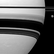 Saturn's largest moon, Titan, looks small here, pictured to the right of the gas giant in this Cassini spacecraft view.