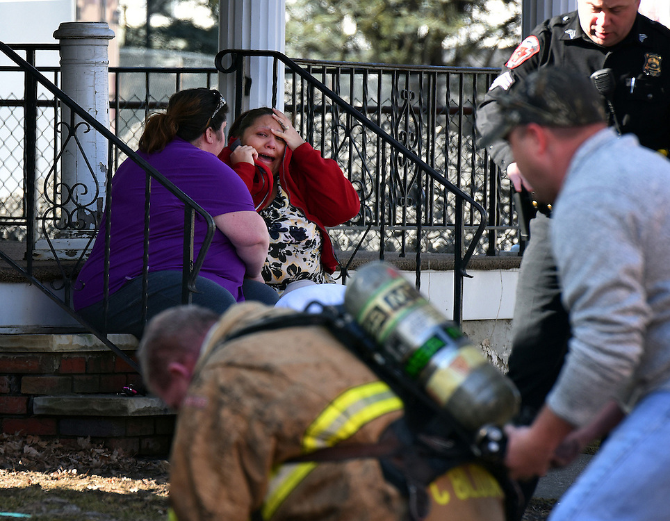 A woman cries on a neighbors porch while watching as firemen extinguish a fire at her home.