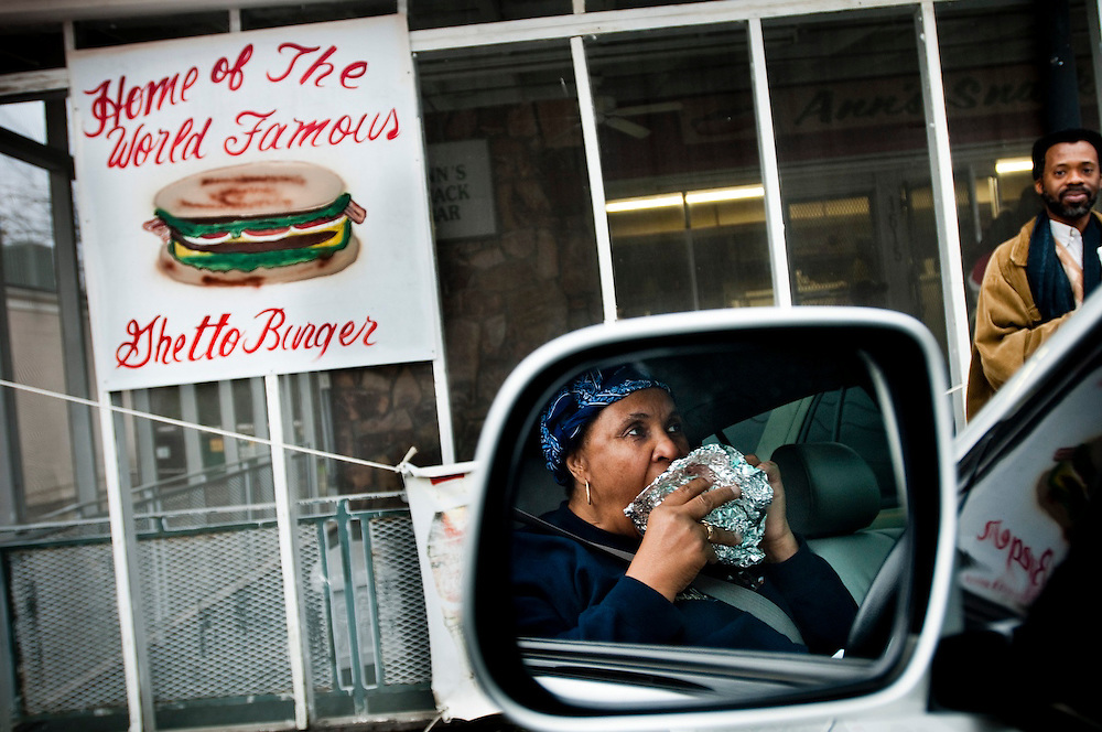 "Mildred Burn enjoying a Ghetto Burger in her car outside Miss Ann's Snack Bar...Ann's Snack Bar in the Atlanta neighborhood Kirkwood..The small restaurant is owned and operated by Ann Price, known to patrons as ""Miss Ann"" and has been in operation since 1973.  The house special is called the ""Ghetto Burger"", a double bacon chili cheeseburger with a secret ingredient.Wall Street Journal named the Ghetto Burger the best hamburger in America."