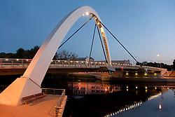 Lighted arched bridge over river Emajõgi in Tartu at night, Estonia
