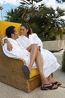 Couple in bathrobes embracing in wicker chair outdoors
