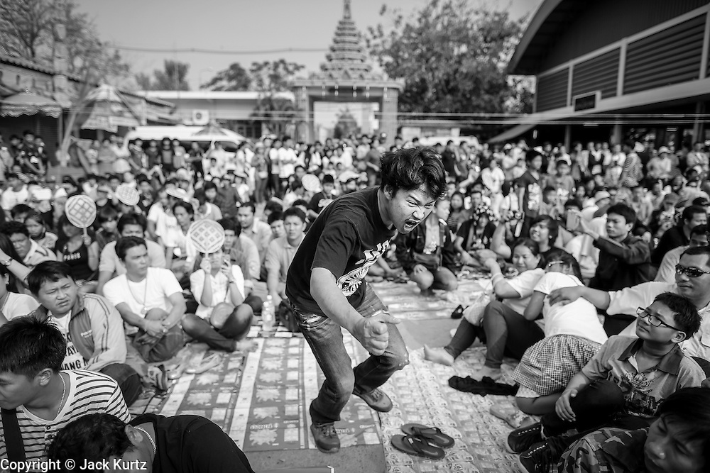 "15 MARCH 2014 - NAKHON CHAI SI, NAKHON PATHOM, THAILAND: A man jumps into the air to rush the stage as he goes into a trance state at the Wat Bang Phra tattoo festival. Wat Bang Phra is the best known ""Sak Yant"" tattoo temple in Thailand. It's located in Nakhon Pathom province, about 40 miles from Bangkok. The tattoos are given with hollow stainless steel needles and are thought to possess magical powers of protection. The tattoos, which are given by Buddhist monks, are popular with soldiers, policeman and gangsters, people who generally live in harm's way. The tattoo must be activated to remain powerful and the annual Wai Khru Ceremony (tattoo festival) at the temple draws thousands of devotees who come to the temple to activate or renew the tattoos. People go into trance like states and then assume the personality of their tattoo, so people with tiger tattoos assume the personality of a tiger, people with monkey tattoos take on the personality of a monkey and so on. In recent years the tattoo festival has become popular with tourists who make the trip to Nakorn Pathom province to see a side of ""exotic"" Thailand.   PHOTO BY JACK KURTZ"