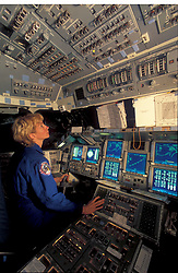 Stock photo of a woman sitting in a NASA training simulator preparing for a flight