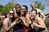 """Members of the Victoria's Secret team stop for a group photo after getting some of the mud off after their games during MuddyGras, the 20th annual mud volleyball for Epilepsy at Wegerzyn Gardens MetroPark in Dayton, Saturday, July 10, 2010. Tori Grewe of Dayton (13) says it's the teams first year, and though they lost, both games were close.  """"We're rookies,"""" she added."""
