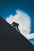 Climber enjoying slab climber in cold winter day with lenticular clouds in La Pedriza, Spain