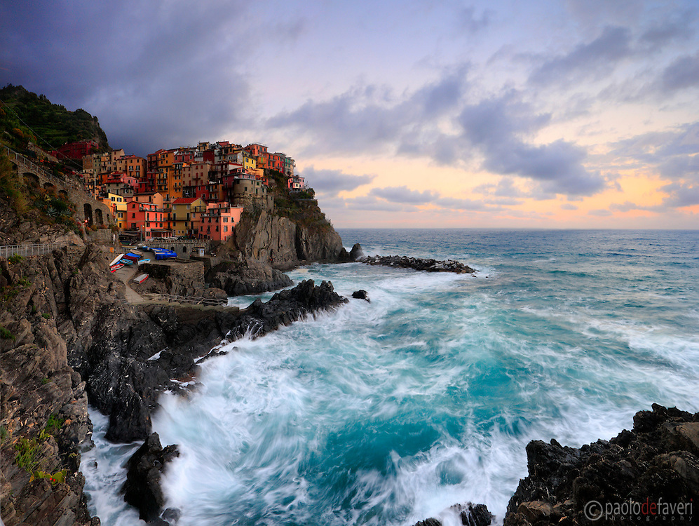 A view at dawn of the beautiful small fishermen village of Manarola, one of the five villages altogether known as Cinque Terre. Taken about 15 minutes before sunrise on a morning at the end of May, just after a storm with strong winds.