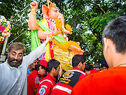 31 AUGUST 2014 - SARIKA, NAKHON NAYOK, THAILAND: A statue of Ganesh is unloaded from a truck before being submerged during the Ganesh Festival at Shri Utthayan Ganesha Temple in Sarika, Nakhon Nayok. Ganesh Chaturthi, also known as Vinayaka Chaturthi, is a Hindu festival dedicated to Lord Ganesh. It is a 10-day festival marking the birthday of Ganesh, who is widely worshiped for his auspicious beginnings. Ganesh is the patron of arts and sciences, the deity of intellect and wisdom -- identified by his elephant head. The holiday is celebrated for 10 days, in 2014, most Hindu temples will submerge their Ganesh shrines and deities on September 7. Wat Utthaya Ganesh in Nakhon Nayok province, is a Buddhist temple that venerates Ganesh, who is popular with Thai Buddhists. The temple draws both Buddhists and Hindus and celebrates the Ganesh holiday a week ahead of most other places.    PHOTO BY JACK KURTZ