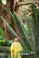 Boy Standing by Large Fern