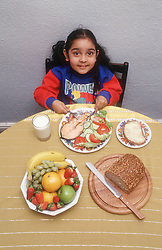 Young girl eating healthy meal of fish; bread; fruit and salad,