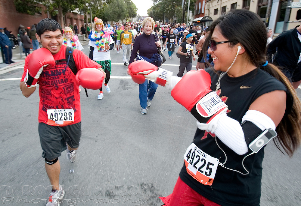 Christopher Agacite of Signal Hill, Calif., left, spars with Toni Oasay of Seaside, Calif. as they run along Hayes Street during the 100th running of the Bay to Breakers 12K through San Francisco, Sunday, May 15, 2011. (Photo by D. Ross Cameron)