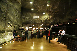 General view inside the 'Wieliczka' Salt Mine, in Wieliczka, Poland on September 2, 2017. The mine is one of the largest tourist attractions in Poland, registered on the UNESCO list and visited by over a million tourists every year. Opened in the 13th century, the mine produced table salt continuously until 2007, as one of the world's oldest salt mines in operation. Commercial mining was discontinued in 1996 due to low salt prices and mine flooding. The mine is currently one of Poland's official national Historic Monuments, whose attractions include dozens of statues and four chapels carved out of the rock salt by the miners, as well as supplemental carvings made by contemporary artists. The Wieliczka salt mine reaches a depth of 327 meters and is over 287 kilometres long. The rock salt is naturally grey in various shades, resembling unpolished granite rather than the white or crystalline look that many visitors may expect. In the 13th century, rock salt was discovered in Wieliczka and the first shafts were dug. The Saltworks Castle was built in the late 13th to early 14th century. Wieliczka is now the location of the Krakow Saltworks Museum. Many shafts were dug throughout the time the mine was in operation. Different technology was added such as the Hungarian-type horse treadmill and Saxon treadmills to haul the salt to the top of the surface. During WWII, the shafts were used by the occupying Germans as an ad hoc facility for various war-related industries. The mine features an underground lake; and the new exhibits on the history of salt mining, as well as a 3.5 kilometres touring route (less than 2% of the length of the mine's passages) that includes historic statues and mythical figures carved out of rock salt in distant past. More recent sculptures have been fashioned by contemporary artists. The Wieliczka mine is often referred to as 'the Underground Salt Cathedral of Poland'. In 1978 it was placed on the original UNESCO list of the World Heritage Sites.