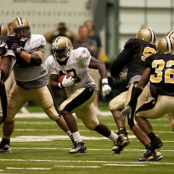 08 August 2009: Rookie running back P.J. Hill (43) runs through a hole during the New Orleans Saints annual training camp Black and Gold scrimmage held at the team's indoor practice facility in Metairie, Louisiana.