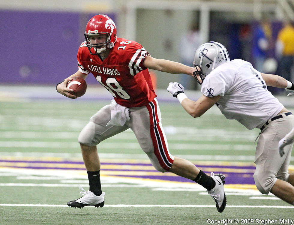City High quarterback AJ Derby (18) stiff arms Xavier end Chase Kleopfer (1) in their Class 4A semifinal game at the UNI Dome in Cedar Falls on Friday November 13, 2009.