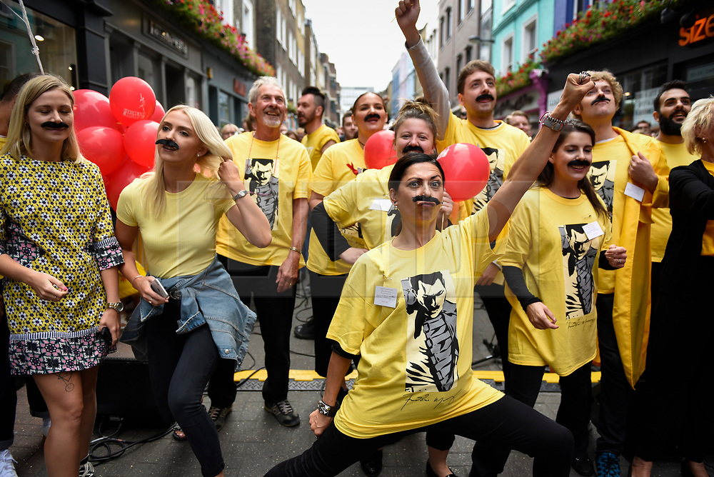 """© Licensed to London News Pictures. 05/09/2018. LONDON, UK. Fundraising volunteers prepare to join fans of Freddie Mercury and members of the public in Carnaby Street donning moustaches during """"Freddie for a Day"""", a fundraising event in aid of the Mercury Phoenix Trust on Freddie Mercury's birthday.  Queen tribute band """"Bulsara and the Queenies"""" sang iconic songs entertaining crowds.  Photo credit: Stephen Chung/LNP"""