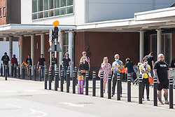 © Licensed to London News Pictures. 25/04/2020. Salford, UK. A queue of socially-distancing shoppers forms around the car park of a branch of Sainsbury's in Salford as supermarkets operating in the UK maintain measures to limit the number of customers in store at any one time and ensure staff and shoppers stay safe during the Coronavirus outbreak . Photo credit: Joel Goodman/LNP