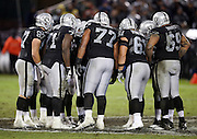 The Oakland Raiders offense huddles and calls a play during the NFL week 12 regular season football game against the Kansas City Chiefs on Thursday, Nov. 20, 2014 in Oakland, Calif. The Raiders won their first game of the season 24-20. ©Paul Anthony Spinelli