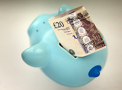 Embargoed to 0001 Thursday July 26 File photo dated 06/01/15 of money in a piggy bank. Hard-pressed households need stronger action to help them deal with debts and save for a rainy day and a pension, MPs have urged.