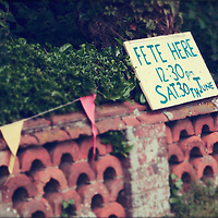 Old brick wall with bunting and sign to small summer fete in the village of Brome & Oakley in Suffolk, England.