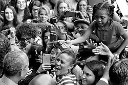 Former President Barack Obama interacts with fans and supporters as he works the rope line after rallying for Democratic candidates top for election in the November Mid-term Elections.