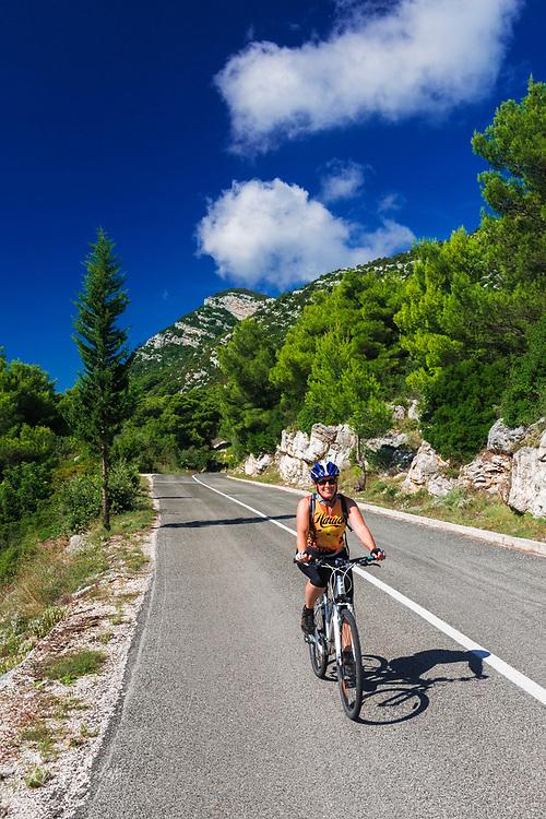 Cyclist on the road into Sobra, Mljet Island, Croatia