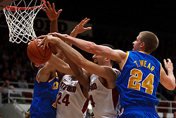 Dec 29, 2011; Stanford CA, USA;  UCLA Bruins forward Travis Wear (24) knocks a loose ball away from Stanford Cardinal center Stefan Nastic (second from right) and forward Josh Huestis (24) during the first half at Maples Pavilion.  Mandatory Credit: Jason O. Watson-US PRESSWIRE