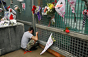Mourners leave flowers on the fence around the World Trade Center site including this man who quietly wept  for his girlfriend Angela Rosario whose name appeared on a list of 9/11 heros.