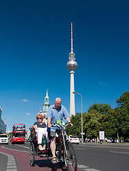 Tourists in tricycle on street with Fernsehturm or Television Tower to rear in Alexanderplatz in Mitte Berlin Germany