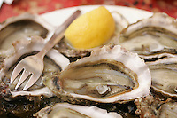 .Oysters served on the weekends at the Paris Wine Bar, Baron Rouge..a perfect example of a symbiotic business relationship, oyster farmer Bernard Delis arrives every weekend from November to April with a truck load of his oysters from the Bay of Archachon, near Bordeaux..He opens them outside the bar and they are served with lemon, and bread and butter, a traditional method..The bar is always jammed with plates of oysters on every conceivable surface, including the hoods, trunks,  and rooves of the parked cars.. - Photograph by Owen Franken