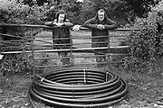 Men standing behind fence near water pipes, Glastonbury, Somerset, 1989
