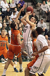 01 March 2014:  Peter Smith stands in front of a shot by Pat Sodemann during an NCAA mens division 3 CCIW  Championship basketball game between the Wheaton Thunder and the Illinois Wesleyan Titans in Shirk Center, Bloomington IL