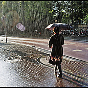 Nederland, Utrecht, 27-08-2011 Vrouw loopt alleen in de regen in de regen  in Nobelstraat . Foto: Gerard Til / Hollandse Hoogte
