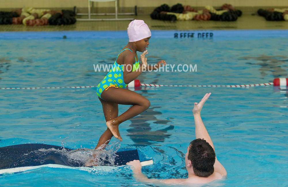 Middletown, New York - A young girl runs off the end of a floating mat during swimming lessons at the YMCA of Middletown on Nov. 4, 2014.