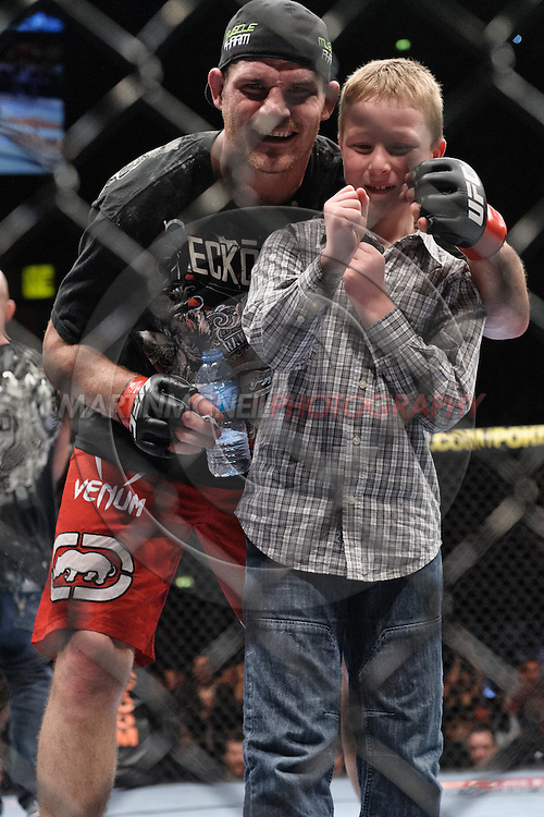 """MANCHESTER, ENGLAND, NOVEMBER 14, 2009: Michael Bisping poses with his son, Callum, following his victory at """"UFC 105: Couture vs. Vera"""" inside the MEN Arena in Manchester, United Kingdom."""