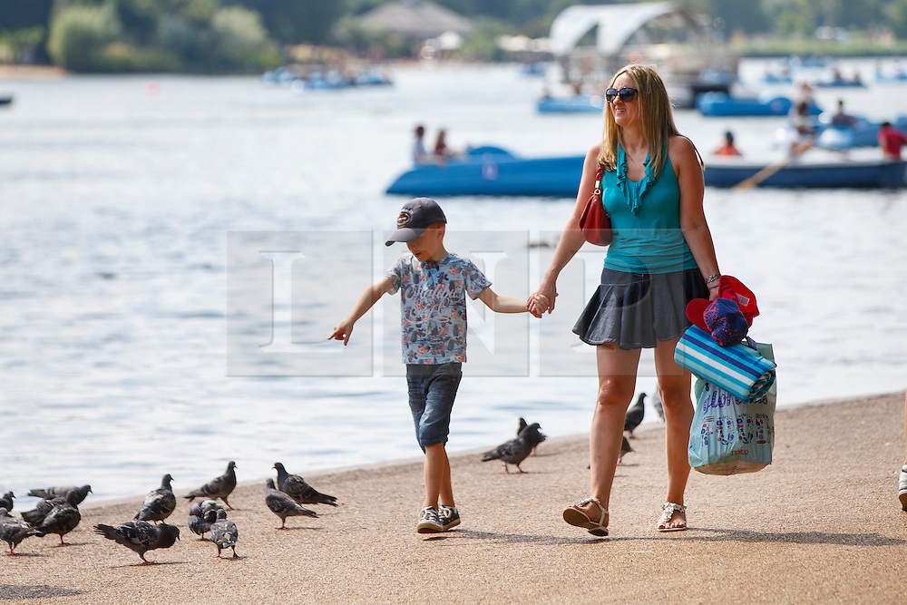 © Licensed to London News Pictures. 20/07/2016. London, UK. People walk around the Serpentine pond and enjoy hot weather in Hyde Park, London as temperatures hit 27C degrees across the capital on Wednesday, 20 July 2016. Photo credit: Tolga Akmen/LNP
