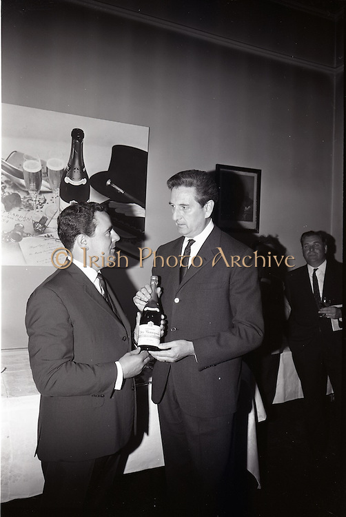 24/06/1965<br /> 06/24/1965<br /> 24 June 1965<br /> Gilbeys Ireland Ltd. reception at Gilbey&rsquo;s Wine Merchants, Nos. 46-49 O&rsquo;Connell St., Dublin, for the presentation of a consignment of Dry Monopole Champagne to the organisers of Le Bal des Petits Lits Blancs. Image shows Mr. David I. Dand (left), Director, Gilbeys of Ireland Ltd. handing over the Champagne to M. Rene Lambert, Chairman, Organising Committee of the ball.