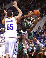Cleveland State guard Joe Davis (4) drives in for a basket over Kansas State's David Hoskins (15) and Jason Bennett (55) in the first half at Bramlage Coliseum in Manhattan, Kansas, December 5, 2006.  K-State beat the Vikings 93-60.<br />