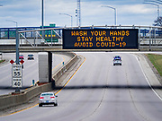 "29 MARCH 2020 - DES MOINES, IOWA: A road sign that normally displays traffic safety messages displays a COVID-19 safety message over I-235 eastbound in downtown Des Moines. On Sunday morning, 29 March, Iowa reported 336 confirmed cases of the Novel Coronavirus (SARS-CoV-2) and COVID-19. There have been four deaths attributed to COVID-19 in Iowa. Restaurants, bars, movie theaters, places that draw crowds are closed until 07 April. The Governor has not ordered ""shelter in place""  but several Mayors, including the Mayor of Des Moines, have asked residents to stay in their homes for all but the essential needs. People are being encouraged to practice ""social distancing"" and many businesses are requiring or encouraging employees to telecommute.         PHOTO BY JACK KURTZ"