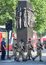 © Licensed to London News Pictures. 25/05/2017. London, UK. Armed soldiers and police walk past the Women of the War memorial in Westminster, London following a terrorist attack in Manchester, northern England, earlier this week. 23 people were killed an dozens more injured when Salman Abedi set off a suicide bomb at an Ariana Grande concert.  Photo credit: Ben Cawthra/LNP