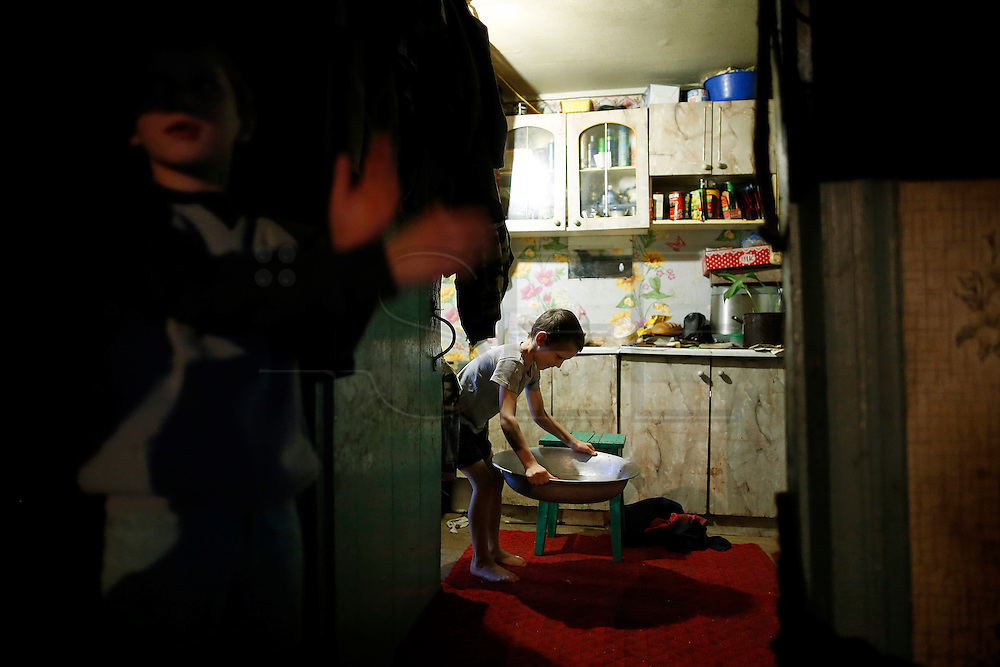 Bogdan, 9 prepares a basin of warm water where he will take a bath.<br /> He lives with his mother, his 3 brothers and his stepfather in a little house with poor living conditions. Last school vacations he went to Portugal and he will return next Summer.