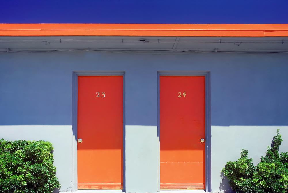Texas motel detail with orange trim,shrubs, and deep blue sky.