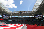 A large American flag covers the field while players stand at attention on the scoreboard during the playing of the National anthem before the Miami Dolphins 2016 NFL week 5 regular season football game against the Tennessee Titans on Sunday, Oct. 9, 2016 in Miami Gardens, Fla. The Titans won the game 30-17. (©Paul Anthony Spinelli)